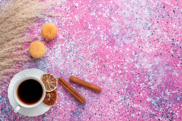 Top view of cup of tea with cinnamon on pink surface