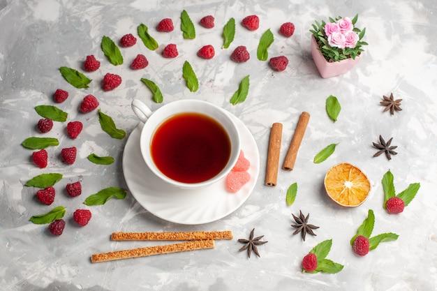 Vista dall'alto tazza di tè con cannella e lamponi sulla superficie bianca cannella di frutti di bosco di tè