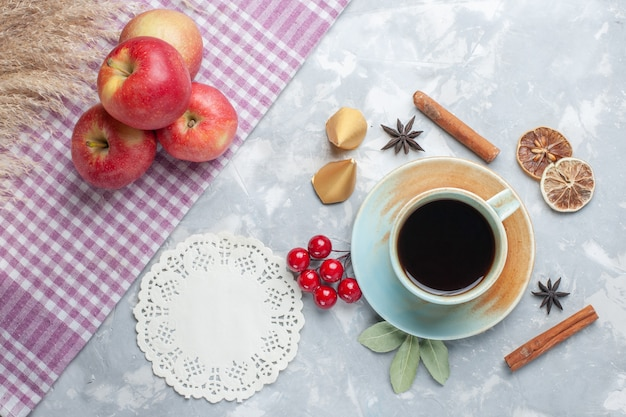 Top view cup of tea with cinnamon red apples and dried lemon slices on the light desk tea candy color breakfast