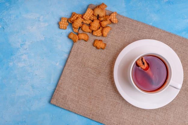Vista dall'alto di una tazza di tè con stecca di cannella e biscotti sul tavolo