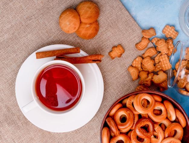 Vista dall'alto di una tazza di tè con biscotti ai bastoncini di cannella e una ciotola con bagel russi sul tavolo