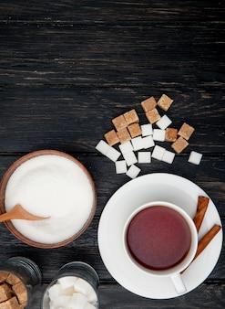 Vista superiore di una tazza di tè con bastoncini di cannella e zucchero semolato bianco in una ciotola di legno e zucchero di grumo su fondo di legno nero