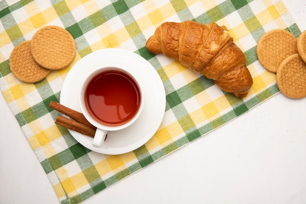 Top view of cup of tea with cinnamon on tea bag and cookies with japanese butter roll on cloth on white background with copy space