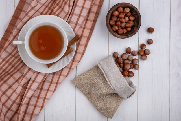 Top view cup of tea with cinnamon on a towel and hazelnuts in a burlap bag on a gray background
