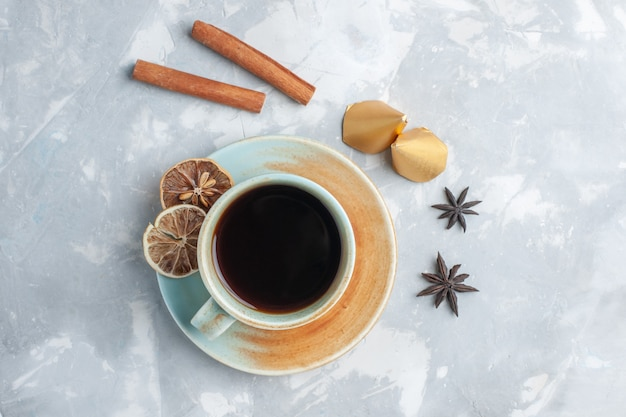 Vista dall'alto tazza di tè con cannella sulla colazione colore caramella tè scrivania bianca