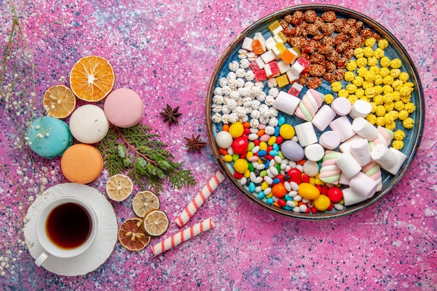 Top view cup of tea with colorful french macarons on pink surface
