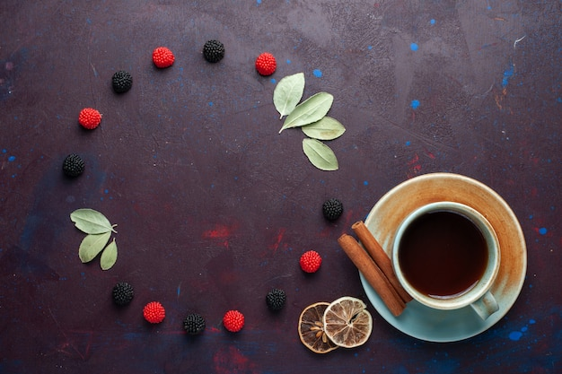 Top view of cup of tea with confiture berries on dark surface