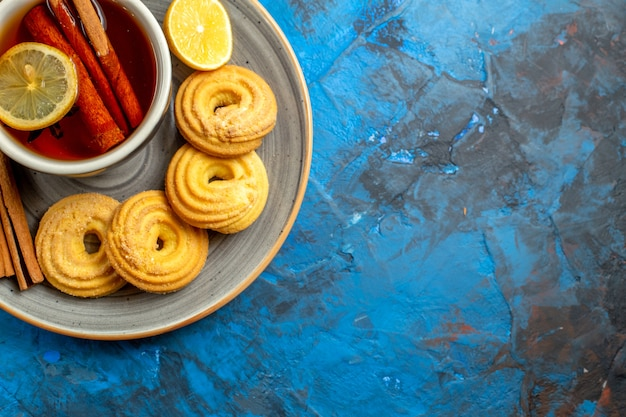 Top view cup of tea with cookies on a blue table biscuit candy tea cookie