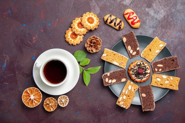 Vista dall'alto tazza di tè con biscotti e fette di torta su uno spazio buio