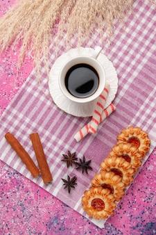 Vista dall'alto tazza di tè con biscotti e cannella sulla scrivania rosa biscotto zucchero biscotto dolce