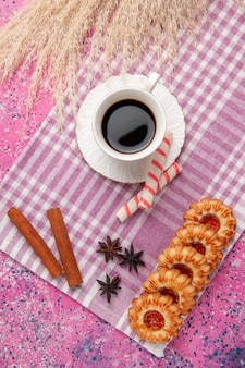 Top view cup of tea with cookies and cinnamon on pink desk biscuit sugar cookie sweet