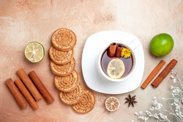 Vista dall'alto tazza di tè con biscotti e cannella sul tavolo bianco biscotto al tè al limone