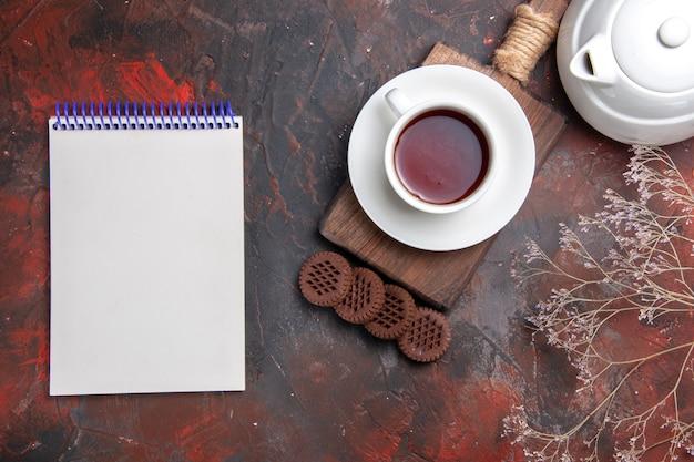 Vista dall'alto tazza di tè con biscotti sulla scrivania scura
