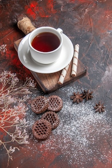 Top view cup of tea with cookies on dark table