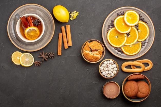 Vista dall'alto tazza di tè con biscotti e arance fresche a fette su biscotto di frutta agli agrumi con superficie scura