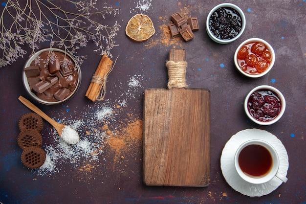Vista dall'alto tazza di tè con biscotti e marmellata su uno spazio buio