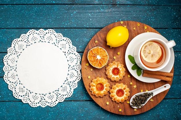 Vista dall'alto tazza di tè con biscotti e limone sulla scrivania blu
