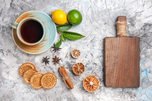 Top view cup of tea with cookies and lemon on a light table biscuit tea fruit