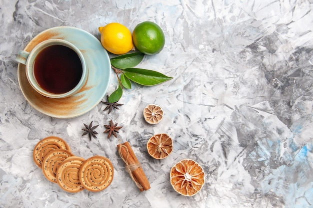 Top view cup of tea with cookies and lemon on light table biscuit tea fruit
