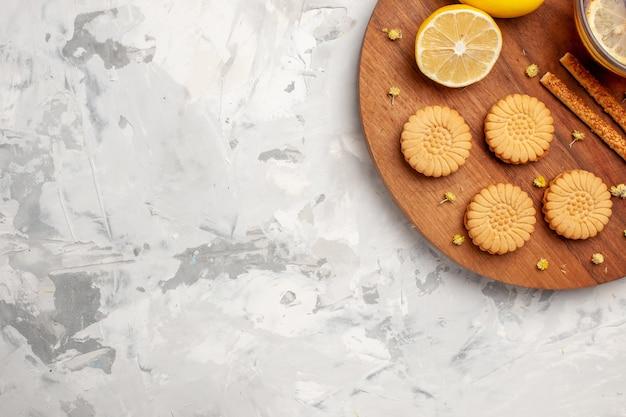 Vista dall'alto tazza di tè con biscotti e limone su uno spazio bianco chiaro