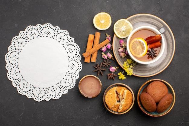 Vista dall'alto tazza di tè con biscotti e fette di limone sulla superficie scura tè zucchero frutta biscotto dolce biscotto