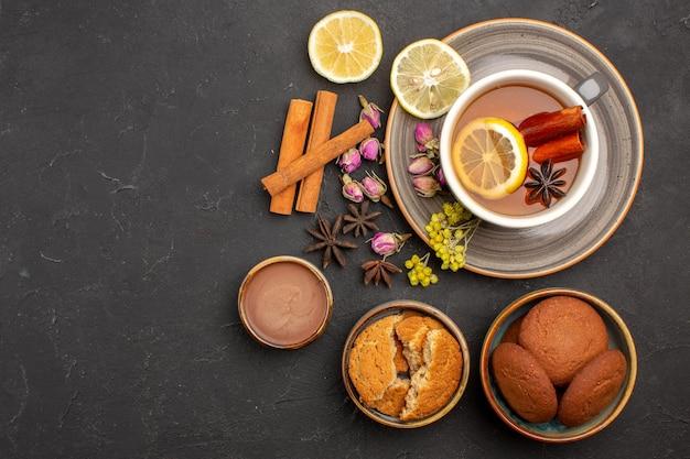 Top view cup of tea with cookies and lemon slices on dark surface tea sugar fruit biscuit sweet cookie