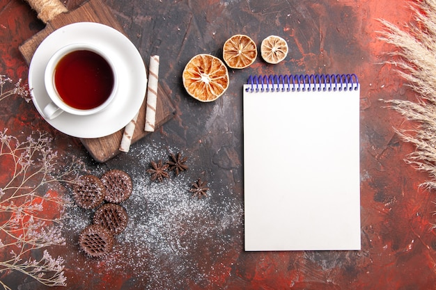 Top view cup of tea with cookies and notepad on dark table biscuit dark ceremony