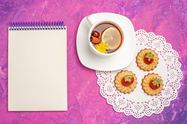 Vista dall'alto tazza di tè con biscotti sul tavolo rosa biscotto da tè color caramella