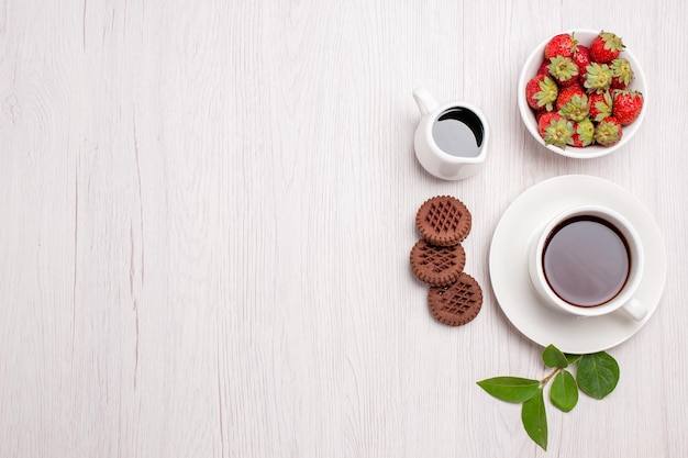 Top view cup of tea with cookies and strawberries on white desk sugar tea cookies sweet biscuit