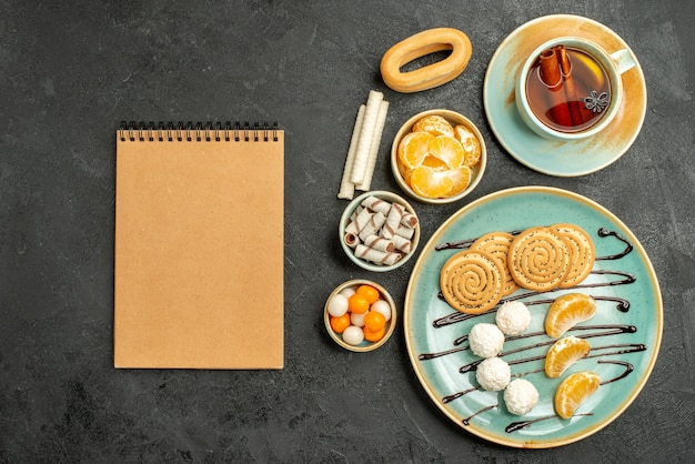 Vista dall'alto tazza di tè con biscotti e mandarini sulla scrivania grigio scuro