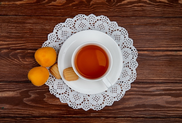 Top view of cup of tea with cookies in teabag and apricots on wooden background