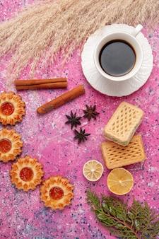 Vista dall'alto tazza di tè con biscotti e cialde sul colore rosa della torta dolce dello zucchero del biscotto della scrivania
