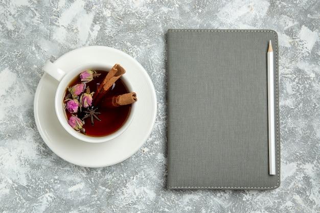 Vista dall'alto tazza di tè con quaderno su sfondo bianco tè bevanda calda dolce zucchero colazione