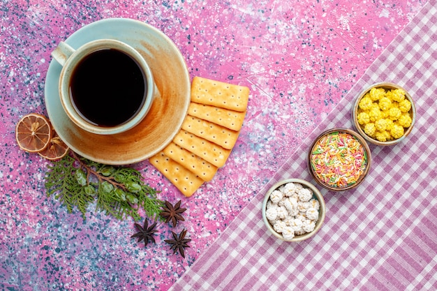 Top view cup of tea with crackers and candies on pink desk