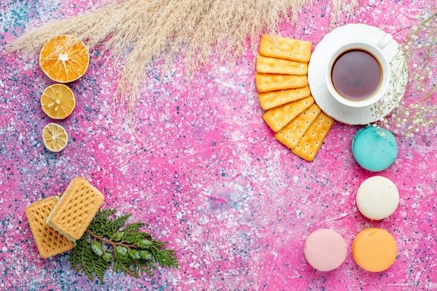 Vista dall'alto tazza di tè con cracker francesi macarons e waffle sulla scrivania rosa