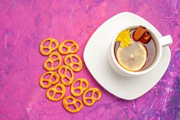 Vista dall'alto tazza di tè con cracker sul tavolo rosa color caramella tè al limone