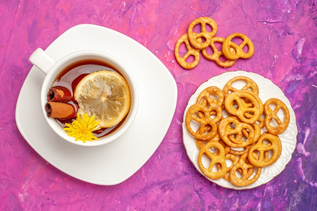 Top view cup of tea with crackers on pink table color lemon candy tea