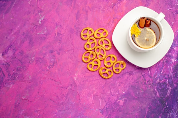 Top view cup of tea with crackers on pink table lemon candy color tea