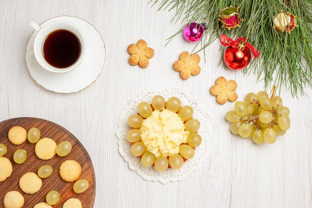 Top view cup of tea with cream cake and grapes on a white desk fruit tea dessert cream biscuit cake