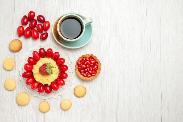 Vista dall'alto tazza di tè con torta cremosa e frutta sulla scrivania bianca