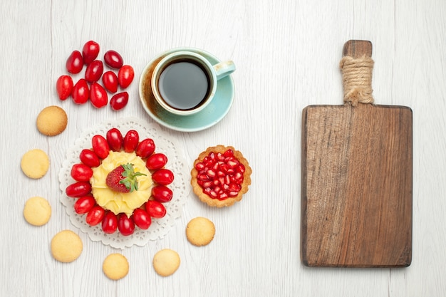 Vista dall'alto tazza di tè con torta cremosa e frutta sul pavimento bianco