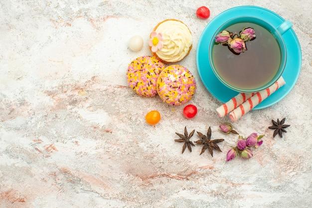 Vista dall'alto tazza di tè con torte cremose su torta di torta di biscotto dessert di tè di superficie bianca