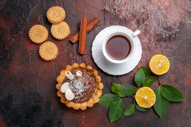 Top view cup of tea with delicious cake and cookies on dark table sweet dessert biscuit