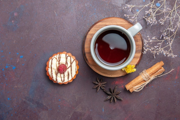 Top view cup of tea with delicious cake on dark background tea cake sweet pie cookie biscuit