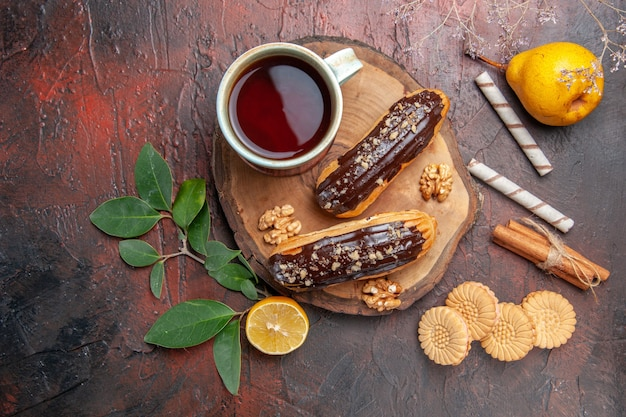 Top view cup of tea with delicious choco eclairs on a dark table cake sweet dessert