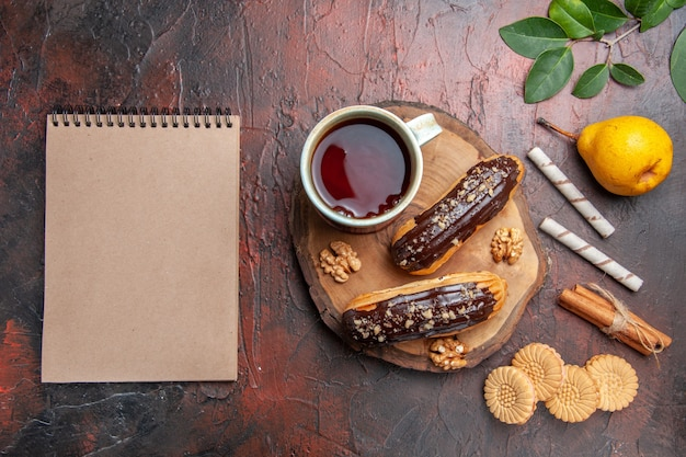 Top view cup of tea with delicious choco eclairs on a dark table sweet biscuit cake