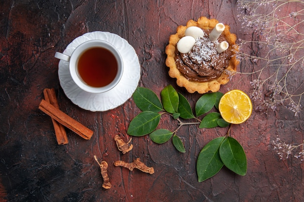 Top view cup of tea with delicious little cake on dark table cookie dessert biscuits