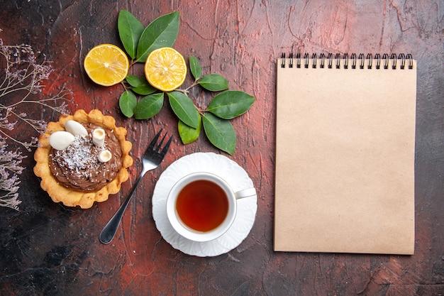 Vista dall'alto tazza di tè con deliziosa piccola torta sul tavolo scuro, biscotto dolce