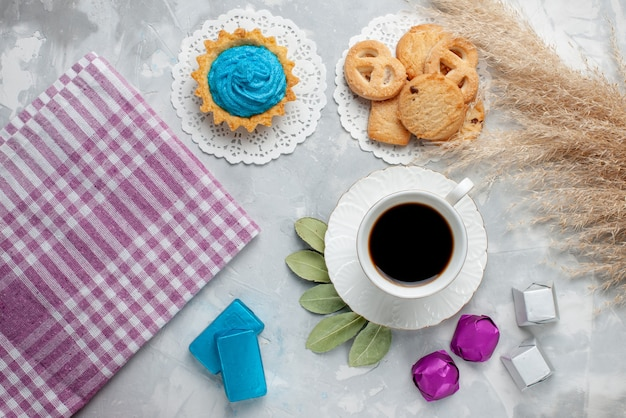 Top view of cup of tea with delicious little cookies chocolate candies on white floor, cookie biscuit candy chocoalte