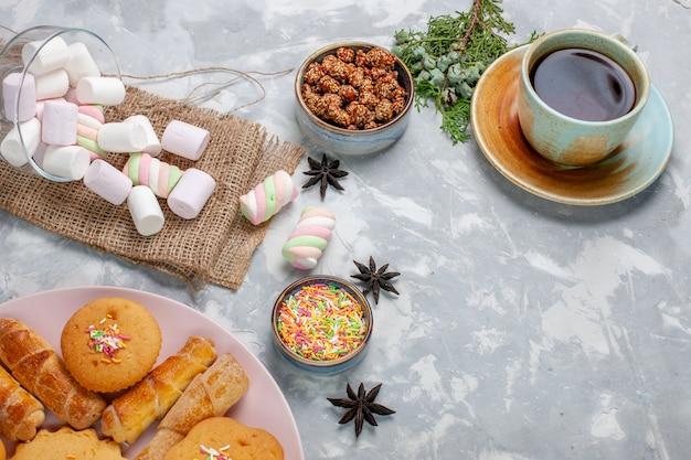 Vista dall'alto tazza di tè con deliziosi piccoli marshmallow e torte sulla scrivania bianca